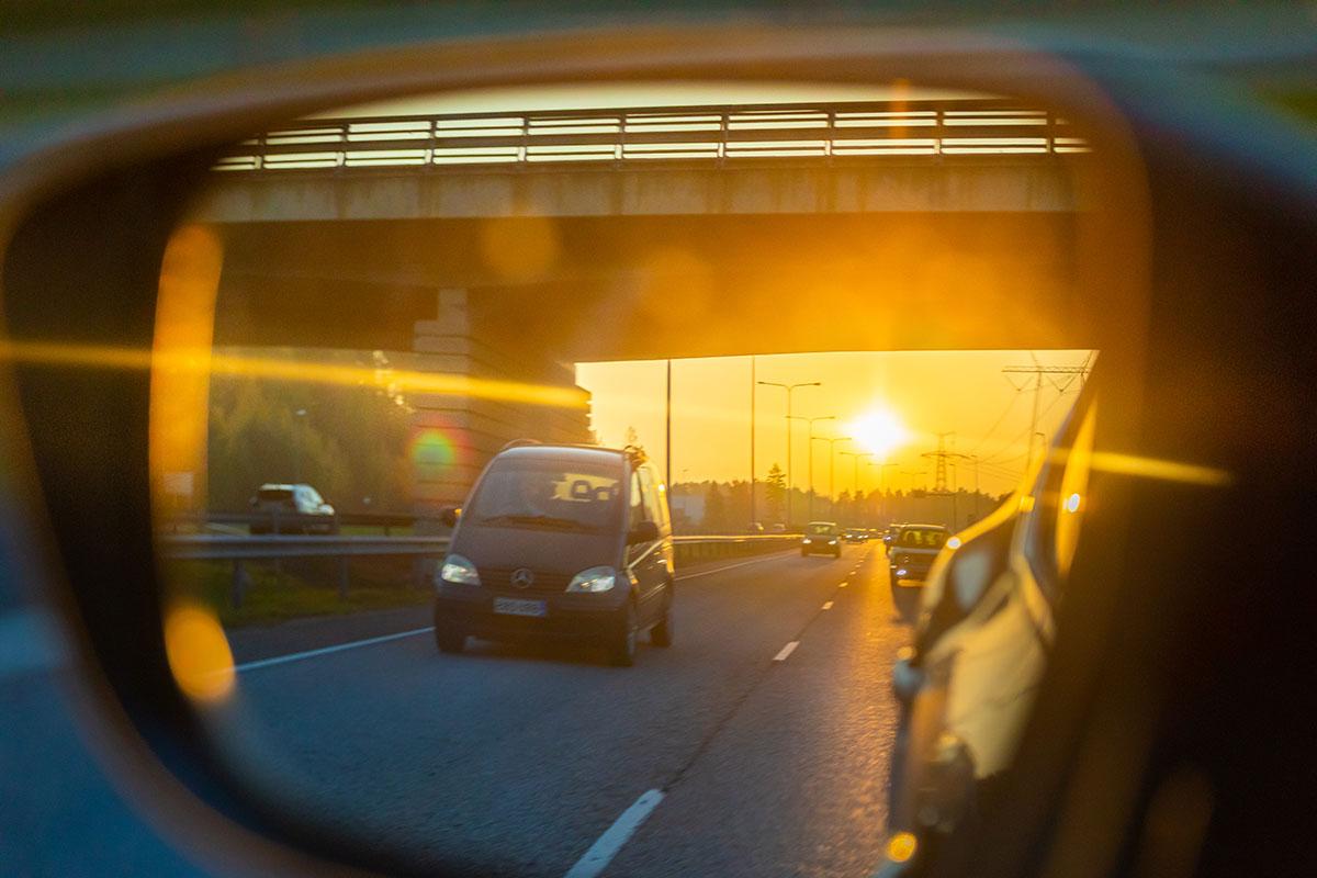 Ilta-auringossa taustapeilissä liikenettä maantiellä